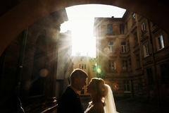 Beautiful blonde bride hugging handsome happy groom at sunset, n. Ewlywed couple kissing in old street, victorian architecture in the background stock photo