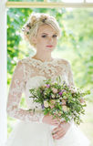 Beautiful blonde bride in a luxurious dress. Portrait of beautiful young girl outdoors in spring Stock Image