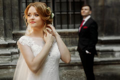Beautiful blonde bride in luxury white wedding dress posing outd. Oors in italian street, face closeup of gorgeous newlywed woman, groom standing in the Royalty Free Stock Photo