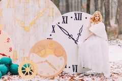 d9de2a1e96f Beautiful blonde bride standing at the big vintage clocks in autumn forest.  Creative wedding decorations
