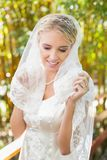Beautiful blonde bride touching her veil and smiling Stock Photos