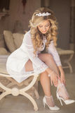 Beautiful blonde bride wearing white wedding shoes, girl with cu Royalty Free Stock Image