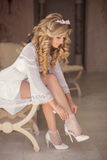 Beautiful blonde bride wearing white wedding shoes, girl with cu Stock Image