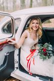 Beautiful blonde bride in white vintage car. Autumn forest on background.  Stock Image