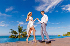 Beautiful blonde bride in white wedding dress and the groom danc. E in a hotel near the infinity pool. Tropical sea, sky and palm trees in the background. Summer Stock Images
