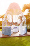 Beautiful blonde bride in white wedding dress and the groom in a. White gazebo at the hotel. Tropical skies and palm trees in the background. Summer vacation Stock Photography