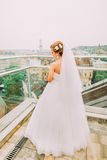 Beautiful blonde bride in white wedding dress looking down at the balcony of luxury hotel room Stock Images