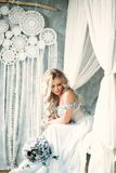 Blonde Bride Woman with Flower Arrangement. Beautiful Blonde Bride Woman with Flower Arrangement, Bridal Hairstyle and Wedding Dress Stock Photography