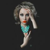 Beautiful blonde with bright makeup and jewelry Royalty Free Stock Photography
