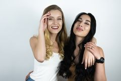 Beautiful blonde and brunette hugging and smiling white background stock photography