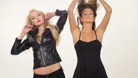 Beautiful blonde and brunette sexy young women. Girl friends or sisters having fun standing together in pink leather dresses looking at camera on ivory stock video footage