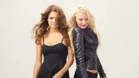 Beautiful blonde and brunette sexy young women. Girl friends or sisters having fun standing together in pink leather dresses looking at camera on ivory stock footage