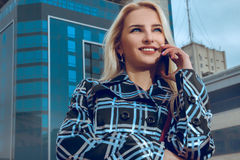 Beautiful blonde business woman with blue eyes talking phone out Stock Images