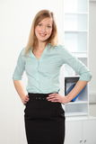 Beautiful blonde business woman standing in office. Big happy smile from beautiful young blonde business woman standing relaxed in office stock photography