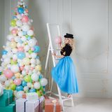 A beautiful blonde in a carnival costume decorates the tree of balloons. Charming young woman in a curvy blue skirt. stock photos