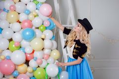 A beautiful blonde in a carnival costume decorates the tree of balloons. Charming young woman in a curvy blue skirt. Royalty Free Stock Photography