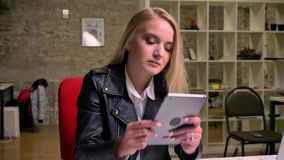 Beautiful blonde caucasian female is sitting at desktop and swiping her tablet and looking concentarted at screet. Indoors, brick office illustration stock footage
