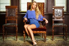 Beautiful blonde on the chateau chair. Beautiful blonde in blue gown sitting on the chateau chair, indoors, chateau environment, fashion photo, studio lighting Stock Photo