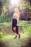 Beautiful blonde at the chateau lake. Beautiful blonde in a evening dress posing at a chateau lake, in a chateau park, fashion photography Stock Photography