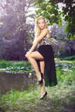 Beautiful blonde at the chateau lake. Beautiful blonde in a evening dress posing at a chateau lake, in a chateau park, fashion photography Stock Photo