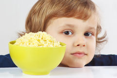 Beautiful blonde child with a bowl of millet porridge Stock Image