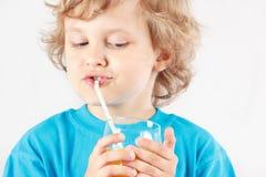 Beautiful blonde child drinking a fresh citrus juice Stock Photography