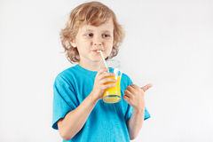Beautiful blonde child drinking a fresh orange juice Royalty Free Stock Images
