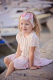 Beautiful blonde child girl portrait on sea side with boats on background. Beautiful curly blonde child girl in pink and white outfit portrait on sea side with Stock Image