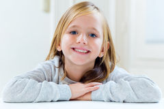Beautiful blonde child sitting at a table in kitchen. Royalty Free Stock Images