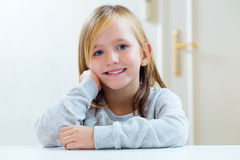 Beautiful blonde child sitting at a table in kitchen. Stock Photography