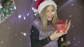 Beautiful blonde Christmas girl with red lantern on background of Christmas decorations stock footage