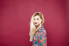 Beautiful Blonde in Colorful Shirt Looking at the Camera and Smiling on Pink Background. Pretty Girl is Posing in Studio Royalty Free Stock Image