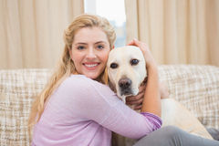 Beautiful blonde on couch with pet dog Stock Photos