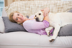 Beautiful blonde on couch with pet dog Royalty Free Stock Photography