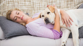 Beautiful blonde on couch with pet dog Stock Images