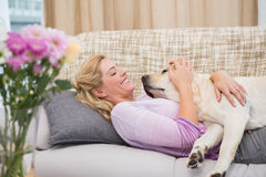 Beautiful blonde on couch with pet dog Royalty Free Stock Photo
