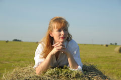 Beautiful blonde country girl sittitng on yellow hay with bunch of flowers Royalty Free Stock Images