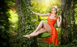 Beautiful blonde with creative haircut on garden swing. Beautiful young woman in orange dress dreaming in a leaves decorated swing between two trees. Gorgeous royalty free stock photo