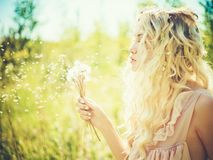 Beautiful blonde with dandelions. Outdoor fashion portrait of romantic blonde with dandelions Stock Image