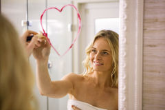Beautiful blonde drawing big heart on mirror. In the bathroom at home stock photography