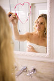 Beautiful blonde drawing big heart on mirror. In the bathroom at home stock photos