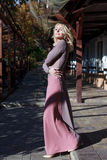 Beautiful blonde in dress walks in autumn Royalty Free Stock Image