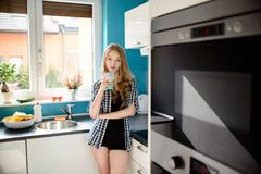 Beautiful blonde dressed in sexy short shorts drinking milk. In the kitchen. The bright, modern kitchen. The girl looks at the camera Stock Image