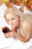 Beautiful blonde is drinking coffee in bed Stock Images