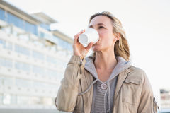 Beautiful blonde drinking of disposable cup Stock Photography