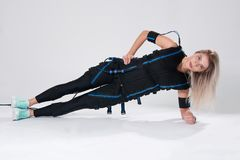 Beautiful blonde in an electric muscular suit for stimulation makes an exercise on the rug. Young woman in EMC suit isolated on white background Stock Photos