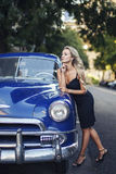 Beautiful blonde elegant girl with blue vintage car Stock Photography