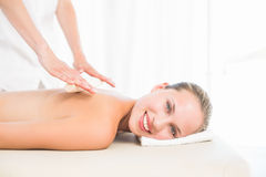 Beautiful blonde enjoying a bamboo roller massage smiling at camera Royalty Free Stock Image