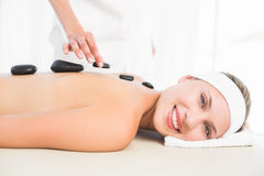 Beautiful blonde enjoying a hot stone massage Royalty Free Stock Images
