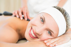 Beautiful blonde enjoying a hot stone massage Stock Photography